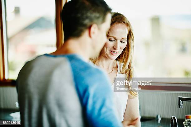 Smiling couple preparing food in home kitchen