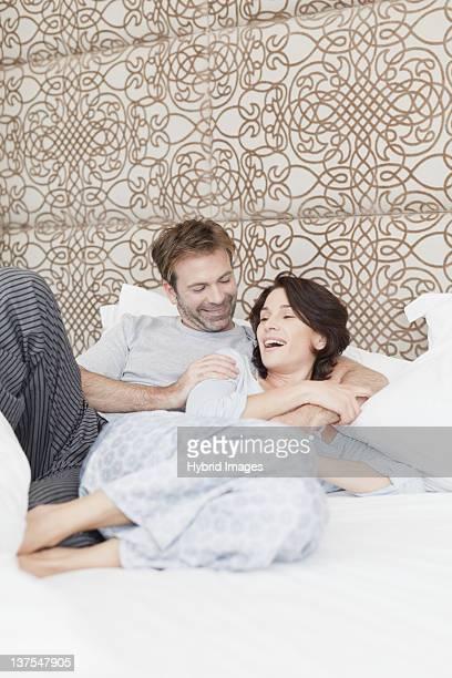Souriant couple de détente au lit