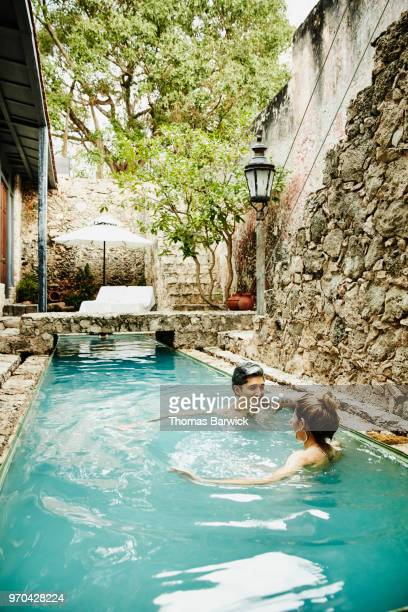 Smiling couple relaxing in courtyard pool of boutique hotel