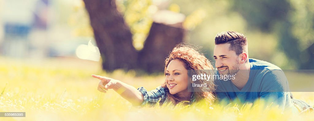 Smiling couple relaxing in grass. : Stock Photo