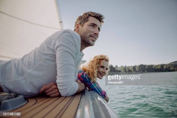 smiling couple relaxing on a sailing boat - mid volwassen koppel stockfoto's en -beelden