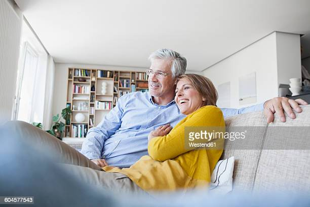 Smiling couple relaxing on the couch at home