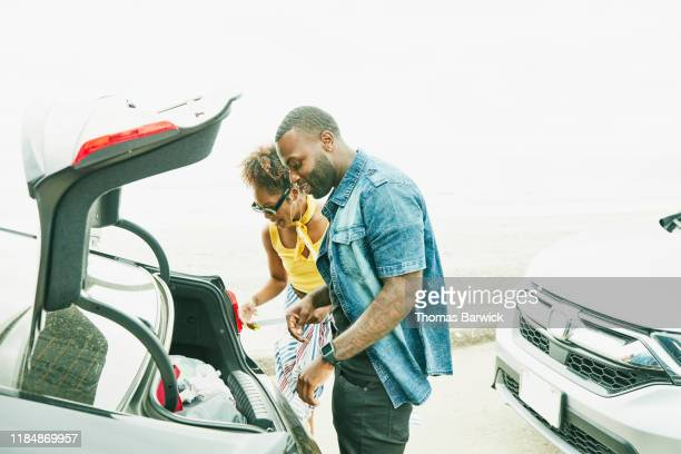 smiling couple removing items from trunk of car before trip to beach on summer afternoon - black boot stock pictures, royalty-free photos & images