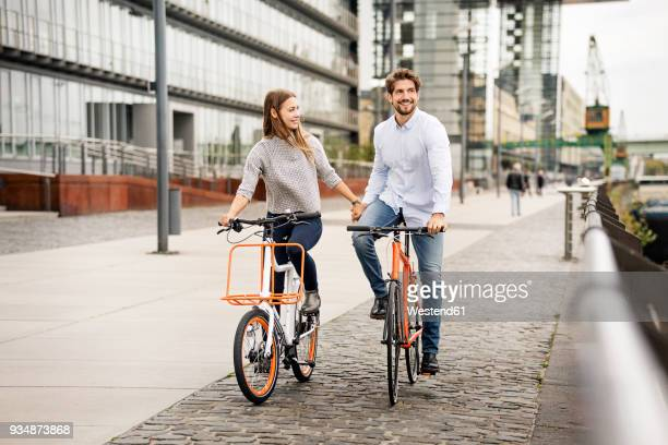 smiling couple riding bicycle in the city - cologne photos et images de collection