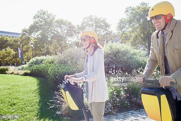Smiling couple riding segway in park, Philadelphia, Pennsylvania, USA