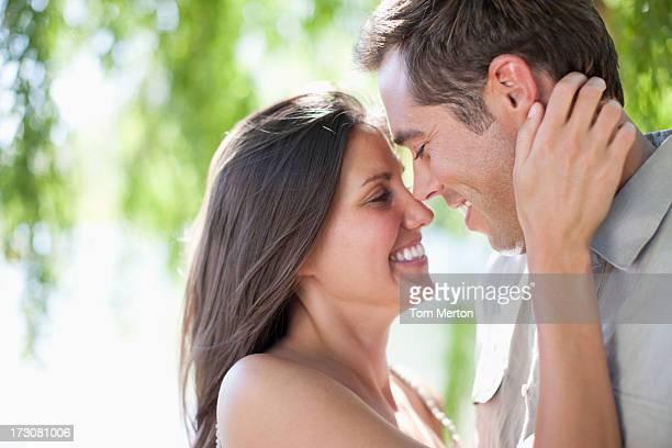 Sorridente coppia Strofinamento del naso all'aperto