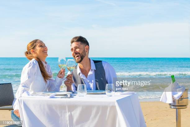 smiling couple sharing romantic dinner beach