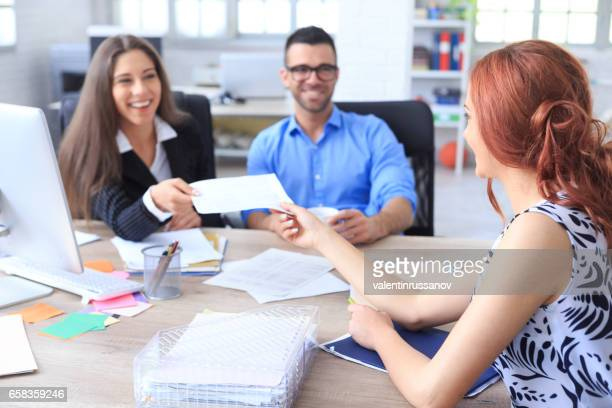 Smiling couple signing agreement in office