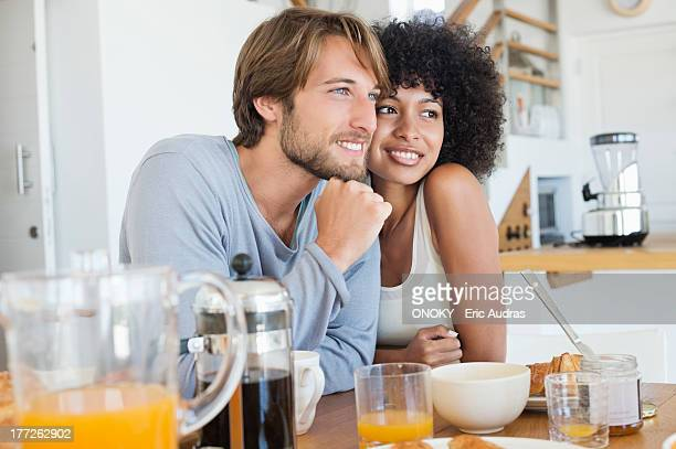 smiling couple sitting at a dining table - afro stock photos and pictures