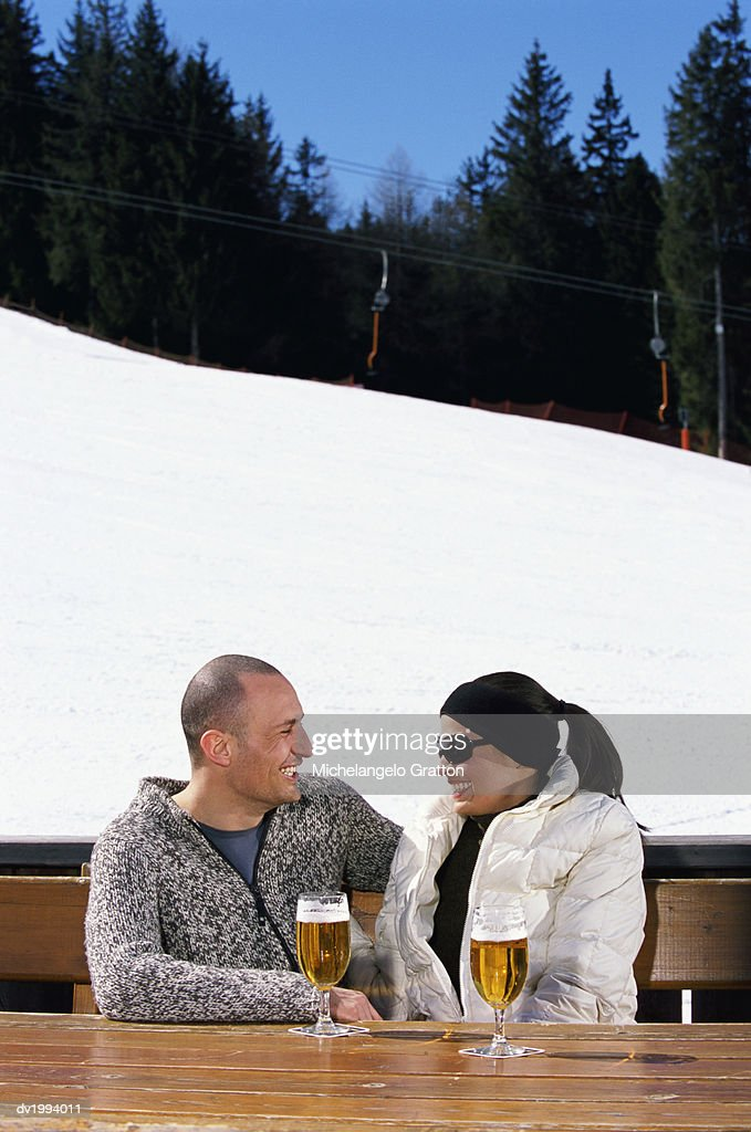 Smiling Couple Sitting at a Table With Lager by a Ski Slope : Stock Photo