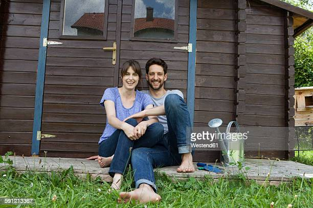 Smiling couple sitting at garden shed