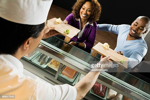 smiling couple sitting at sushi bar - wasabi sauce stock pictures, royalty-free photos & images