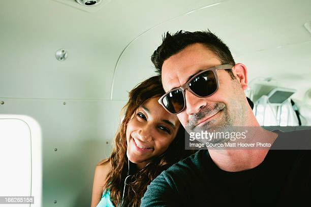 Smiling couple sitting in airplane