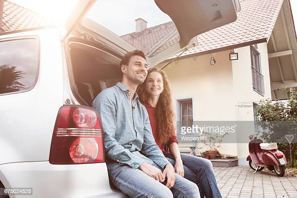 Smiling couple sitting in car trunk at house