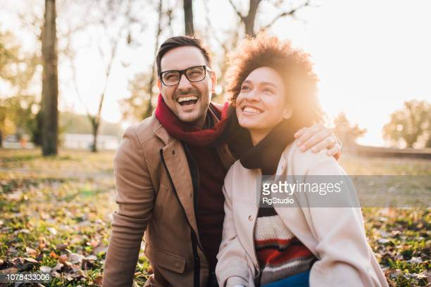 smiling couple sitting in the park - valentines african american stock pictures, royalty-free photos & images