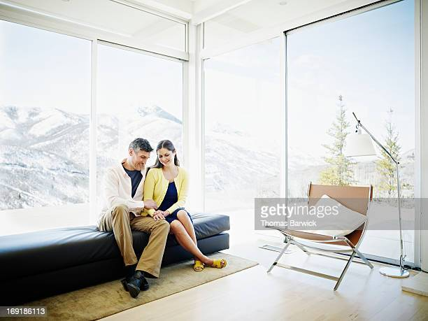 Smiling couple sitting near windows in home