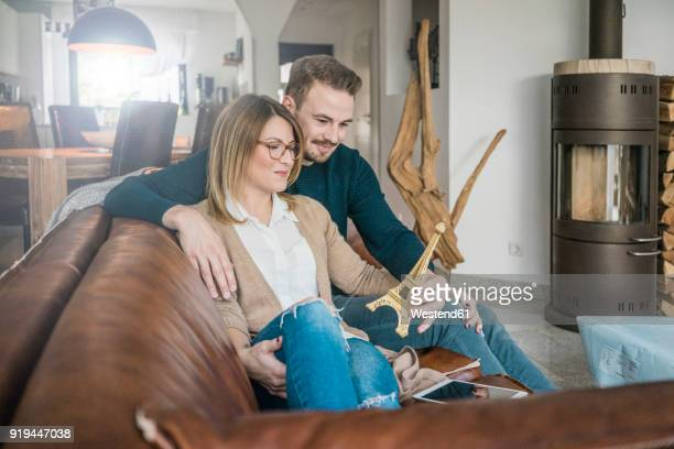 Smiling couple sitting on couch at home with tablet and Eiffel tower model