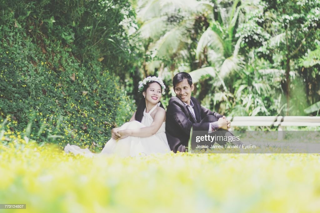Smiling Couple Sitting On Field : Photo