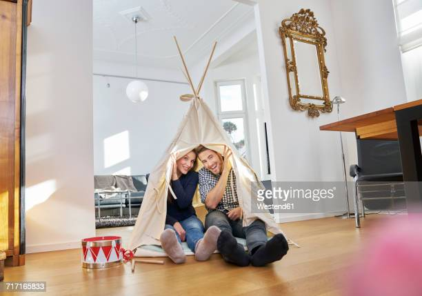 Smiling couple sitting on floor in a teepee