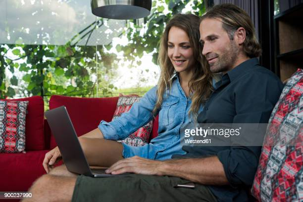Smiling couple sitting on red couch looking at laptop in modern living room with glass facade in background