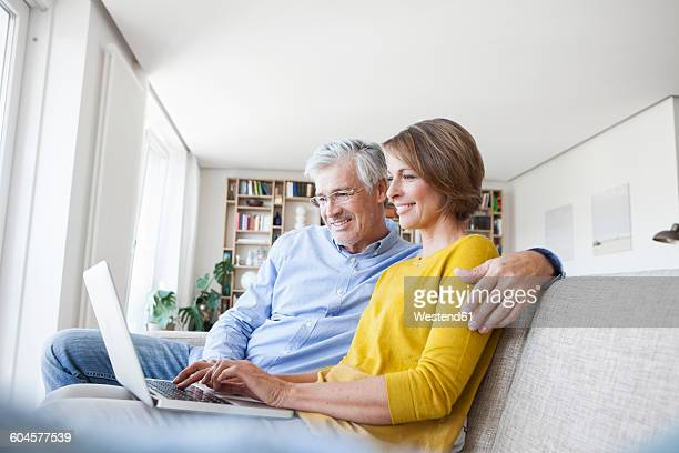 Smiling couple sitting on the couch at home using laptop
