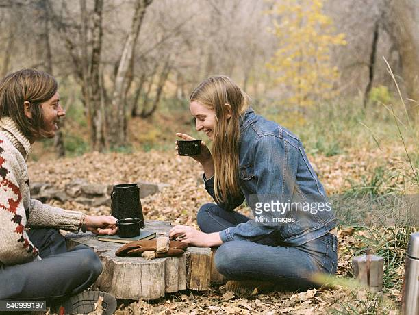 Smiling couple sitting on the ground in a forest, drinking coffee.