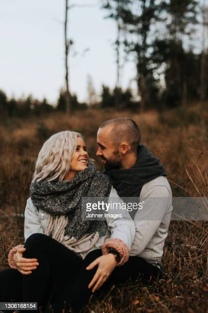 smiling couple sitting together - västra götaland county stock pictures, royalty-free photos & images