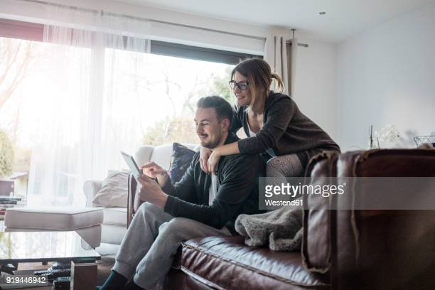 smiling couple sittng on couch at home using tablet - mid adult couple stock pictures, royalty-free photos & images