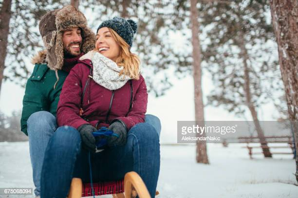 smiling couple sledding in a winter day - winter sport stock pictures, royalty-free photos & images