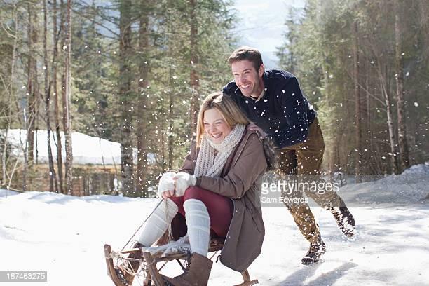 Smiling couple sledding in snow