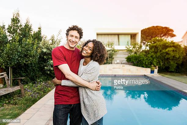 Smiling couple standing against swimming pool