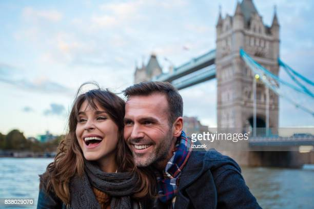 Smiling couple standing against tower bridge london
