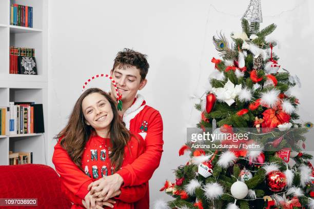 Smiling Couple Standing By Christmas Tree At Home