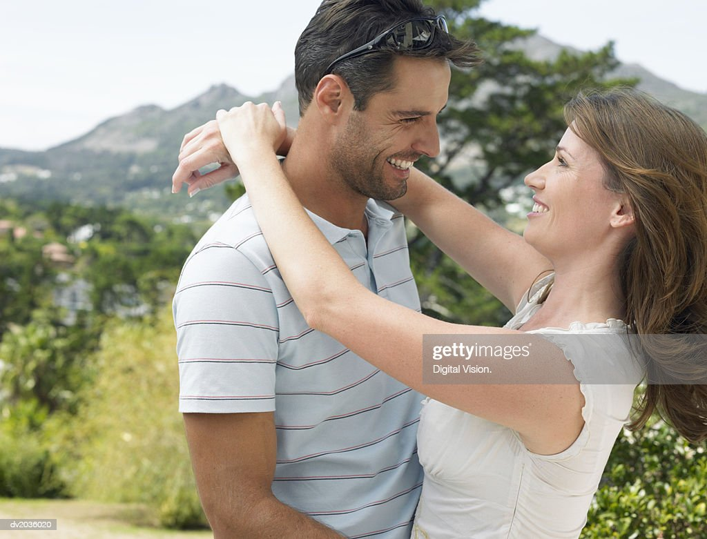 Smiling Couple Standing Face to Face in the Countryside With Their Arms Around Each Other : Stock Photo