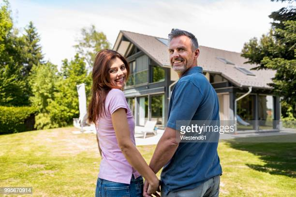 Smiling couple standing hand in hand in garden of their home