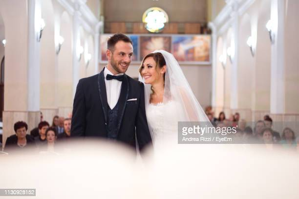 smiling couple standing in church during wedding ceremony - andrea rizzi foto e immagini stock