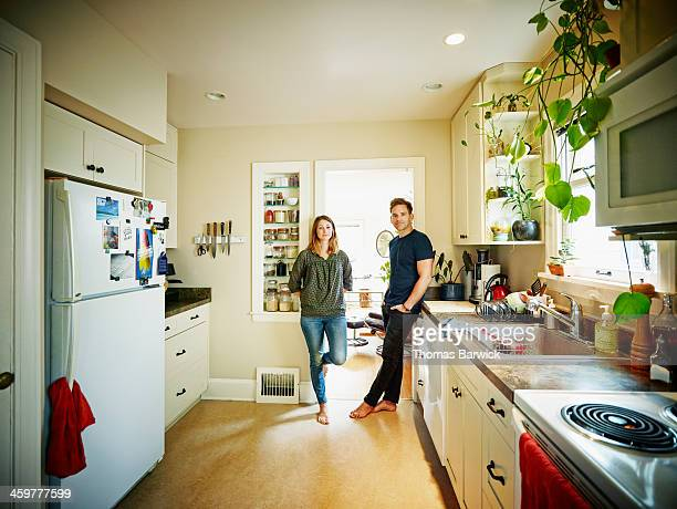 Smiling couple standing in doorway of home kitchen