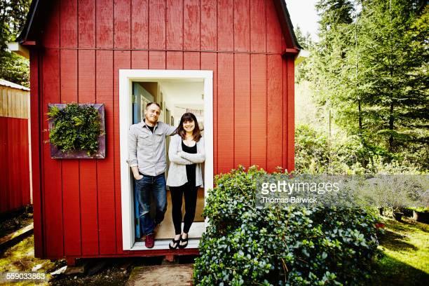 Smiling couple standing in doorway of studio