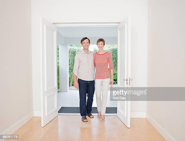 casal sorridente em pé na porta de entrada - entrar imagens e fotografias de stock
