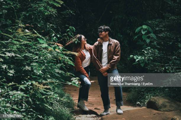 smiling couple standing in forest - reality fernsehen stock pictures, royalty-free photos & images