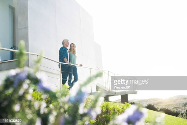 smiling couple standing in front of their modern home - immobilie stock-fotos und bilder