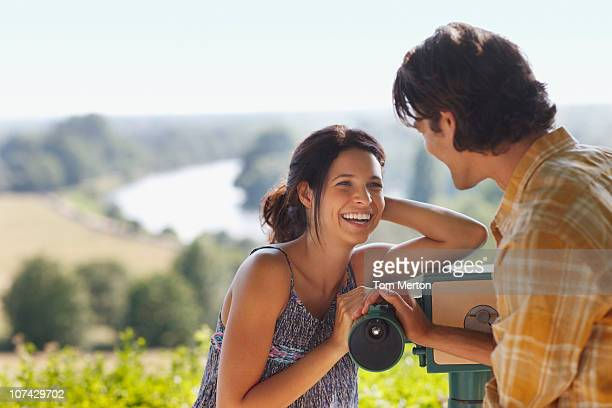 smiling couple standing near hand-held telescope - escaping stock pictures, royalty-free photos & images