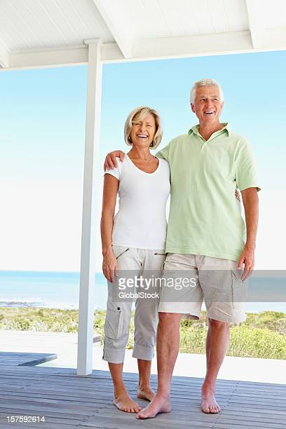 Smiling couple standing together on porch of a beach house