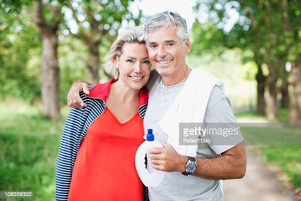 Smiling couple standing together with water bottle