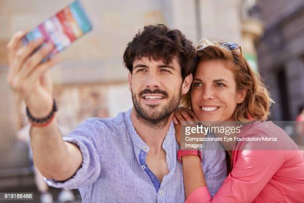 Smiling couple taking selfie on street in Barcelona