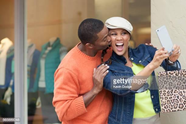 Smiling couple taking selfie outside store
