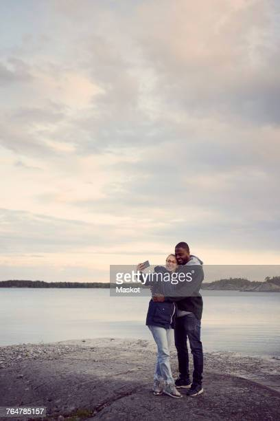 Smiling couple taking selfie while standing at beach against sky during sunset