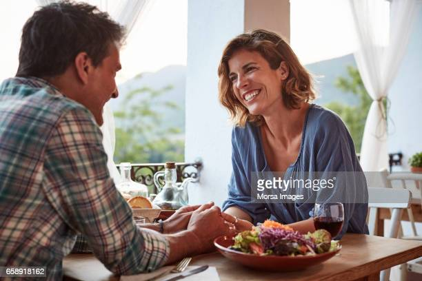 smiling couple talking at restaurant - dating stock pictures, royalty-free photos & images