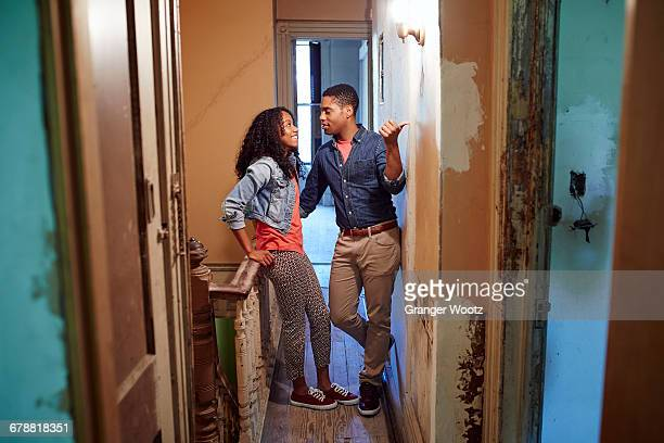 Smiling couple talking in corridor of house under renovation