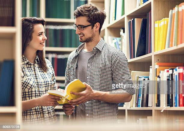 Smiling couple talking to each other in a library.